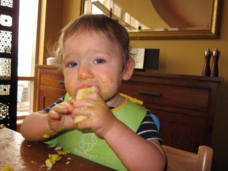 Oliver, age 10 months, enthusiastically chowing down on a banana, scrambled eggs and avocado.