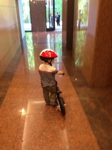 Walking his bike through the lobby of our building.